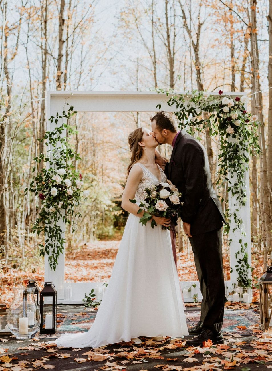 A bride and groom kissing in front of a white square arch in the maple forest