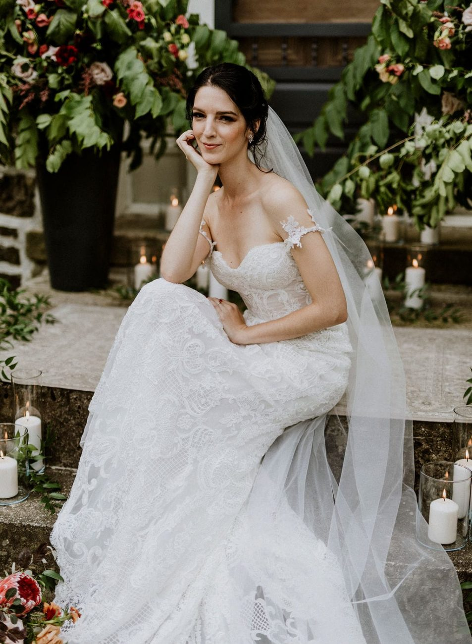 Smiling bride sitting on front steps with candles and flowers around