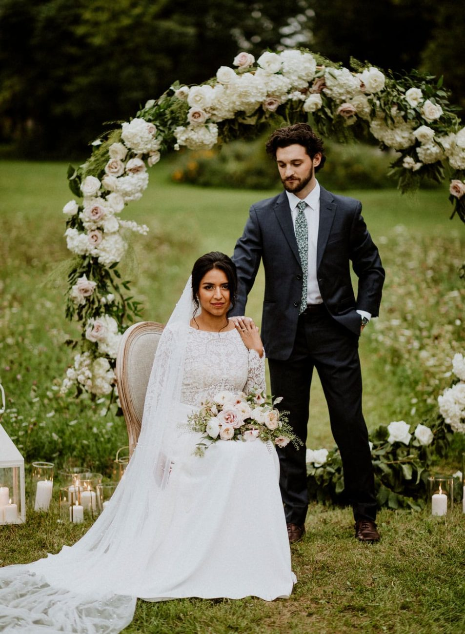 A bride sitting and groom standing beside her in front of large flower arch behind them, in a field